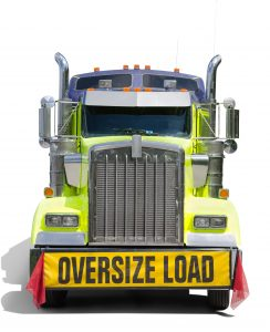 A big semi tractor 18 wheel truck with a big OVERSIZE LOAD banner and red flags on the front of the truck to warn people about the wide load on the truck