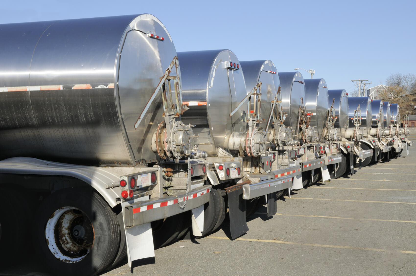 Stainless steel body tanker truck trailers designed for hauling fish lined up on a parking lot in Glaucester, MA.