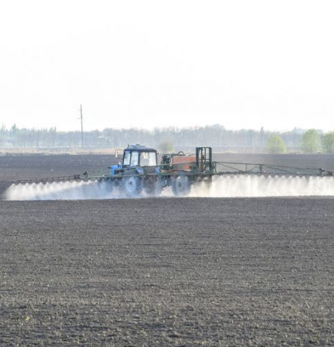 Tractor spraying herbicide chemicals on a field